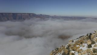 Fog floating through a canyon. Clear blue sky above.