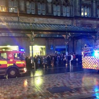 People standing outside a station. Two fire engines are on the road.