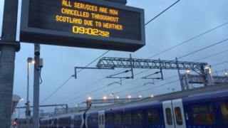 "A train platform sign says ""all services are now cancelled throughout Scotland due to weather"" A train is at the bottom of the picture"