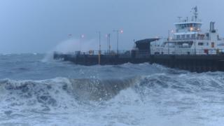 Choppy waves and sea spray around a dock. A ferry is the other side of a docking point.
