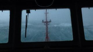The inside of a boat cabin looking out through the windows towards the mast. A huge wave behind it.