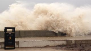 A huge wave soars up over a sea wall.