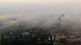 Mist dominates a city panorama. Tall flats and buildings poke out above the blanket.