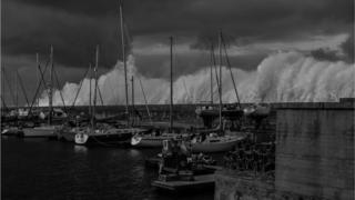 A black and white shot of boats in a harbour. Massive waves crash up and spray over the harbour wall.