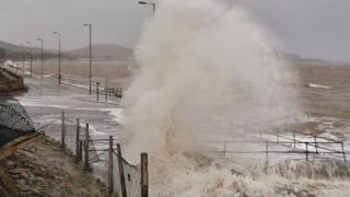 A huge sea spray comes over the sea wall, as high as a tall lamp-post.