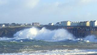 Huge waves crash against land. Tall houses disappear in the spray.
