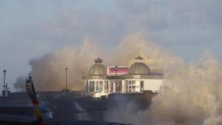 A building on a pier is engulfed by spray from a huge wave.