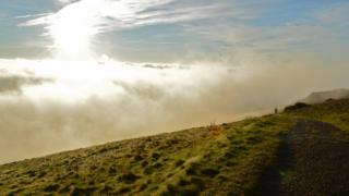 Fog and blue sky dominate the picture. A person is on a footpath on a grassy slope to the right of the picture.