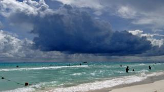 People in a clear blue sea. Large, dark blue clouds are gathering above. Rain is falling from them in the distance.
