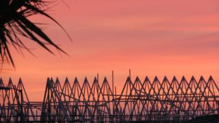 A salmon pink sky. In front are triangle structures and the leaves of a palm tree come into the picture from the left, giving it a tropical feel.