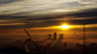 A yellow sun is peaking through grey and gold clouds as it sets. Fog surrounds tall buildings and cranes below.
