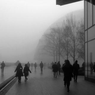 A black and white shot of people walking along the river embankment in fog. A dome building - City Hall - is to the right, behind trees.