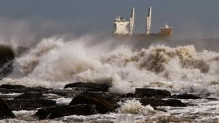 A very choppy sea, with sea spray rising up. A cargo ship is in the distance.