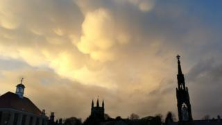 Yellow bulbous clouds in the sky. Spires can be seen from below.