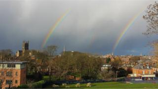 Two rainbows in a grey sky overlook a town and church spires.