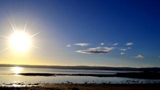 A nearly clear blue sky over the sea. The sun sparkles over the scene.