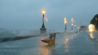 A wet sea front. The lamps are on and the light is blurred in the photograph.