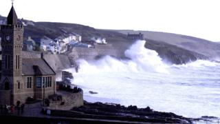 Waves crash against the cliffs. A church and houses are on the left side of the picture.