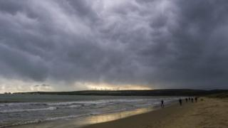 Grey cloudy skies over a beach and sea.