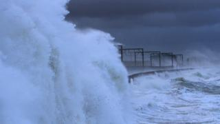 Sea spray rises up and over a railway line. Dark grey clouds above.