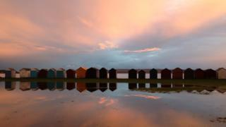 Sea huts reflected in water that surrounds. The sky is cloudy and slightly pink as the sun sets.
