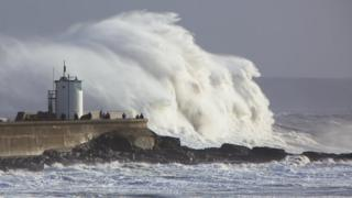 A huge wave crashes against a sea wall and small lighthouse structure. People are standing on the sea wall.