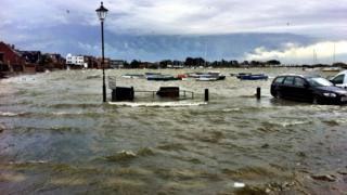A harbour with boats in, has flooded. Water surrounds cars and lamp posts.
