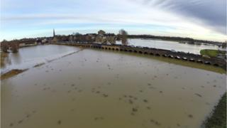 A birds eye view of a river flooding. Water is very close to the arches of a long bridge and it the river has burst its banks.