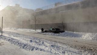 A man shovels snow from around his car on a snow covered street.