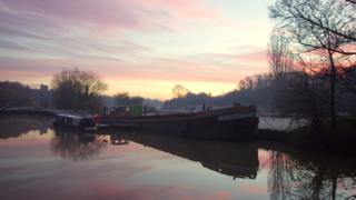 Barges on a canal. The water reflects the grey and pink cloud above.