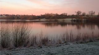 A tinted pink scene of water, frozen land and a pale pink sky.