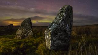 Large stones at night stand in the foreground. Behind is a starry, cloudy sky and green light can be seen between the clouds.