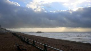 Pebbles from the beach are around benches on the promenade. An old pier can be seen out at sea. A band of cloud and above it is blue sky.