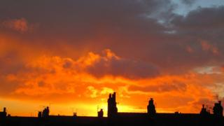 An orange and yellow cloudy sky. Silhouetted rooftops below.