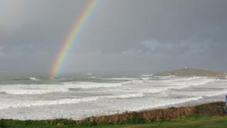 A rainbow in a grey sky lands on top of the sea. A headland can be seen and the waves are frothy.
