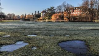 Frozen grass and puddles. Houses, trees and water in the background.