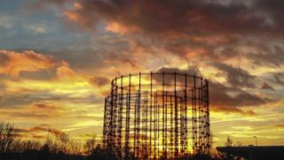 Gas work cylinders. Behind are yellow and grey clouds as the sun sets.