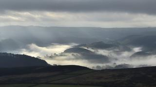 Rolling countryside with mist or fog in the valleys.