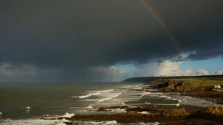 A view of the sea and headlands. A dark cloud above is producing a shower out at sea and a rainbow arches down on to the land.