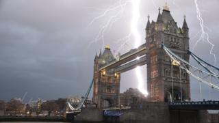 Lightning striking towers that make up the bridge. Grey sky behind.