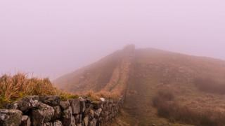 A rocky wall runs through the picture. A pink fog clouds the view.