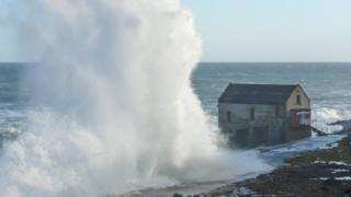 A huge wall of sea spray rises up and towers a building on the seafront. The sea is in the background.