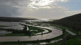 A panorama of flooded fields and river.