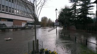 A flooded street. Railings and street signs surrounded by water.