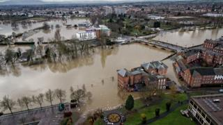 A top shot of a river that is flooding. A bridge going across with cars on. Water is closing in on the arches.