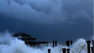 Dark blue-grey clouds over an old, derelict pier. Waves crashing against what is left of the structure.