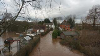 Brown water in streets, surrounds a three houses and gardens and sheds.