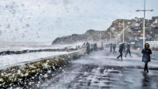 Foamy spray comes on to the promenade by the sea. Onlookers turning away from the sea. Foam spray is on the lens.