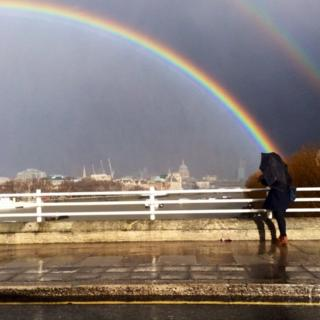 A double rainbow over the River Thames. A person stands looking at it from a bridge, umbrella over them.