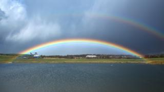 A rainbow, - with half of another rainbow above - over water and grass. Grey sky above.